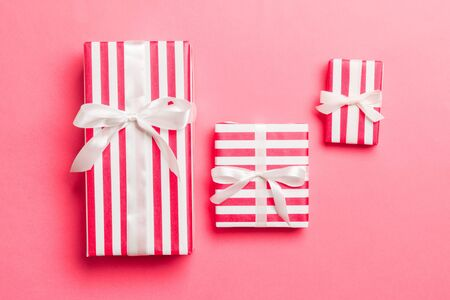 Gift box with White bow for Christmas or New Year day on living coral background, top view.