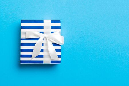 Gift box with white bow for Christmas or New Year day on blue background, top view with copy space.