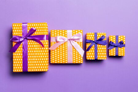 Gift box with purple and pink bow for Christmas or New Year day on purple background, top view.