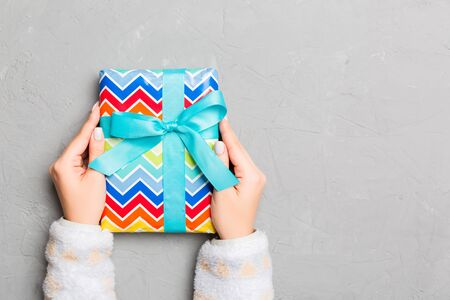 woman hands holding gift wrapped and decorated with colored bow top view on grey cement table Holiday concept with copy space . 스톡 콘텐츠