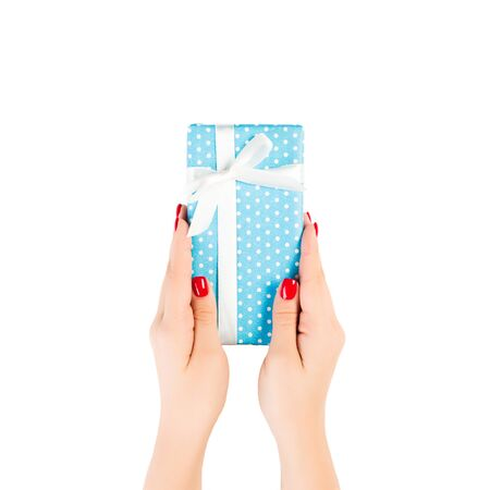 Woman hands give wrapped Christmas or other holiday handmade present in blue paper with white ribbon. Isolated on white background, top view. thanksgiving Gift box concept. Banque d'images