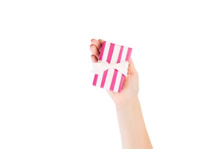 Woman hands give wrapped Christmas or other holiday handmade present in pink paper with white ribbon. Isolated on white background, top view. thanksgiving Gift box concept. 스톡 콘텐츠