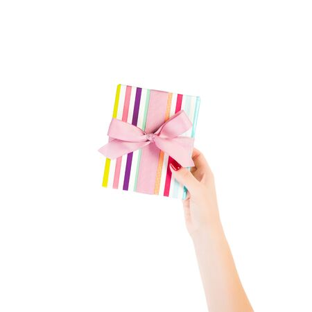 Woman hands give wrapped Christmas or other holiday handmade present in colored paper with pink ribbon. Isolated on white background, top view. thanksgiving Gift box concept. 스톡 콘텐츠