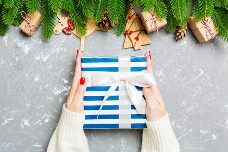 Top view of a woman holding a gift box in her hands on festive cement background. Fir tree and Christmas decorations. New year time concept. Banco de Imagens