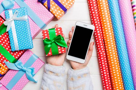 Top view of a woman holding a phone in one hand and a gift in another on wooden background. Rolled up wrapping paper and holiday decorations. Christmas holiday concept. Mockup.