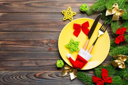 Top view of fork, knife and plate surrounded with fir tree and Christmas decoratoins on wooden background. New Year Eve and holiday dinner concept. Banco de Imagens