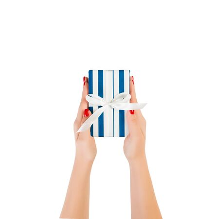 Woman hands give wrapped Christmas or other holiday handmade present in blue paper with white ribbon. Isolated on white background, top view. thanksgiving Gift box concept. Banco de Imagens