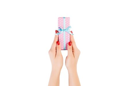 Woman hands give wrapped Christmas or other holiday handmade present in pink paper with blue ribbon. Isolated on white background, top view. thanksgiving Gift box concept.