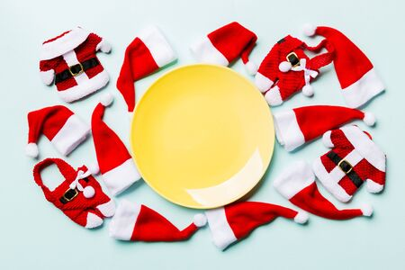 Festive set of plate decorated with Santa Claus hat on colorful background. Top view christmas dinner concept.