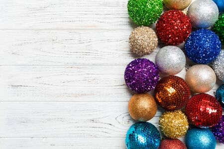 Festive composition of decorative baubles on wooden background. Top view of Christmas toys with copy space.