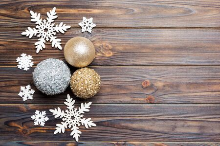 Top view of Christmas balls and creative decorations on wooden background with copy space. New Year concept. Banco de Imagens