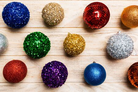 Top view of colorful Christmas balls on wooden background. New Year time concept.