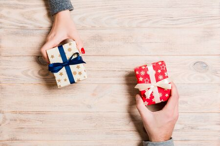 Top view of a woman and a man exchanging gifts on wooden background. Couple give presents to each other. Making surprise for holiday concept with copy space.