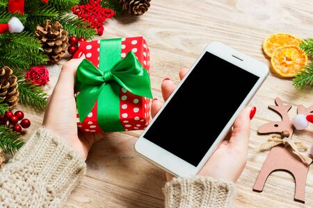 Top view of a woman holding a phone in one hand and a gift in another on wooden background. Fir tree and holiday decorations. Christmas holiday concept. Mockup.