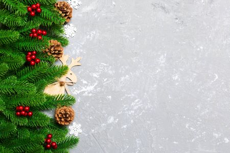 Top view of Christmas background made of fir tree and decorations on cement background. New year holiday concept with copy space. Banco de Imagens