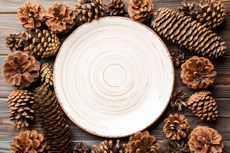 Top view of festive plate with pine cones on wooden background. New Year dinner concept.