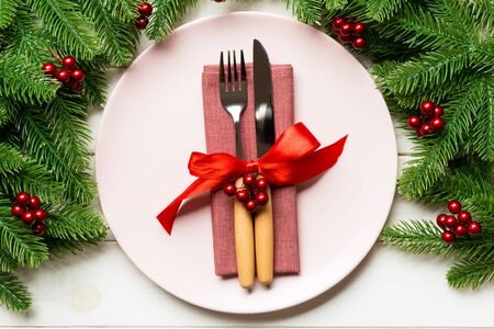Holiday composition of plate and flatware decorated with fir tree on wooden background. Top view of Christmas decorations. Festive time concept.