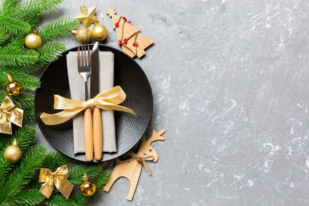 Top view of New Year dinner on festive cement background. Composition of plate, fork, knife, fir tree and decorations. Merry Christmas concept. Banco de Imagens