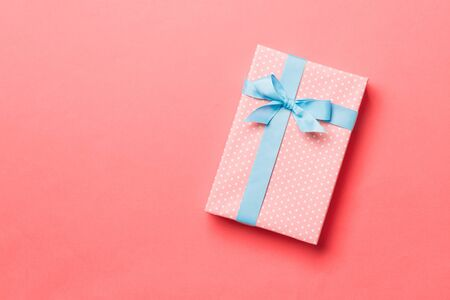 Top view Christmas present box with blue bow on living coral background with copy space. Banco de Imagens