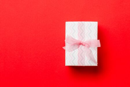 Top view Christmas present box with pink bow on red background with copy space. Banco de Imagens