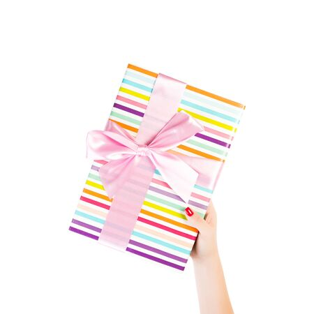 Woman hands give wrapped Christmas or other holiday handmade present in colored paper with pink ribbon. Isolated on white background, top view. thanksgiving Gift box concept. Banco de Imagens