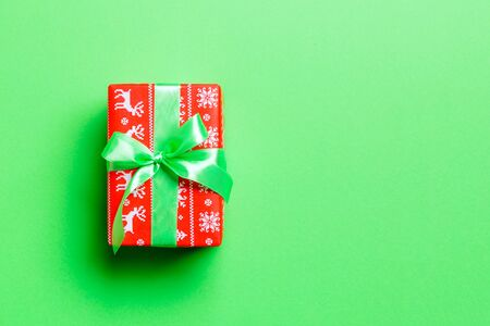 Top view Christmas present box with green bow on green background with copy space.