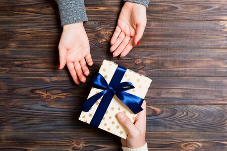 Top view of a woman and a man giving and receiving a present on wooden background. Love and relationship concept. Close up.