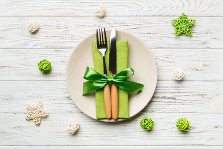 Holiday composition of Christmas dinner on wooden background. Top view of plate, utensil and festive decorations. New Year Advent concept.
