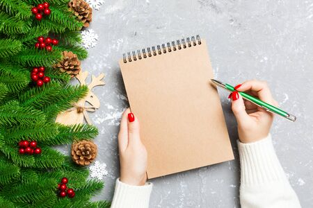 Top view of female hand writing in a notebook on cement Christmas background. fir tree and festive decorations. Wish list. New Year concept.