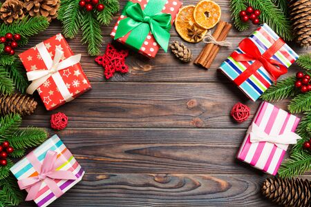 Top view of Christmas background made of fir tree, gifts and other decorations on wooden background. New year holiday concept with copy space.