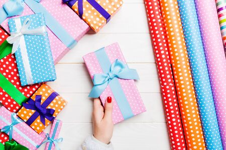 Top view of a woman holding a gift box in her hands on festive wooden background. Rolled up wrapping paper and Christmas decorations. New year time concept.