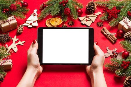 Top view of woman holding tablet in her hands on red background made of Christmas decorations. New Year holiday concept. Mockup.