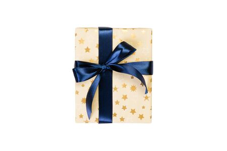 Christmas or other holiday handmade present in gold paper with blue ribbon. Isolated on white background, top view. thanksgiving Gift box concept. 免版税图像
