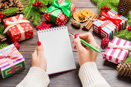 Top view of female hand writing in a notebook on wooden Christmas background. Fir tree and festive decorations. Wish list. New Year concept.