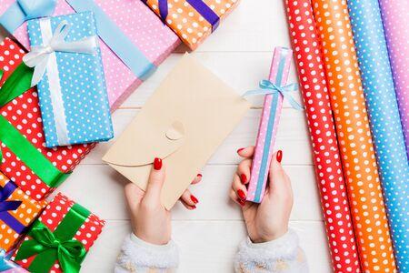 Draufsicht einer Frau, die einen Umschlag in einer Hand und ein kleines Geschenk in einer anderen auf hölzernem Hintergrund hält. Dekorationen für das neue Jahr. Konzept der Weihnachtszeit.