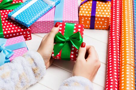 Top view of female hand tie up New Year present on festive wooden background. Gift boxes and rolled up wrapping paper. Christmas time concept. Stock Photo