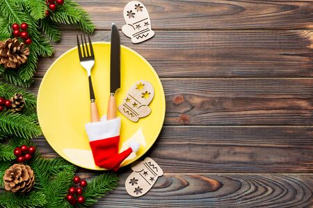 Top view of Christmas dinner on wooden background. Plate, utensil, fir tree and holiday decorations with copy space. New Year time concept. Zdjęcie Seryjne
