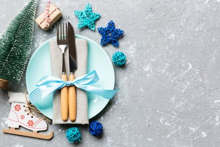 Holiday composition of Christmas dinner on cement background. Top view of plate, utensil and festive decorations. New Year Advent concept with copy space.