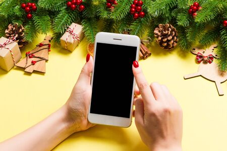 Top view of phone in female hand on festive yellow background. Christmas decorations. New Year time holiday. Mockup.