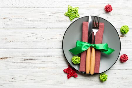 Holiday composition of Christmas dinner on wooden background. Top view of plate, utensil and festive decorations. New Year Advent concept with copy space. Zdjęcie Seryjne