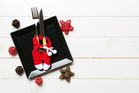 Holiday composition of plate and flatware decorated with Santa clothes on wooden background. Top view of Christmas decorations with empty space for your design. Festive time concept.