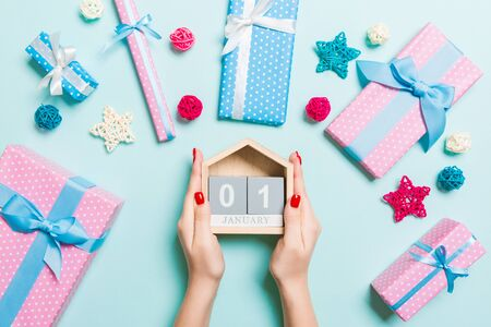 Top view of female hands holding calendar on blue background. The first of January. Holiday decorations. New Year concept.