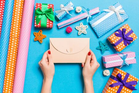 Top view of woman holding an envelope on blue background made of holiday decorations. Christmas time concept.