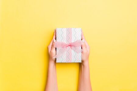 Woman arms holding gift box with colored ribbon on yellow table background, top view and copy space for you design. Stock Photo