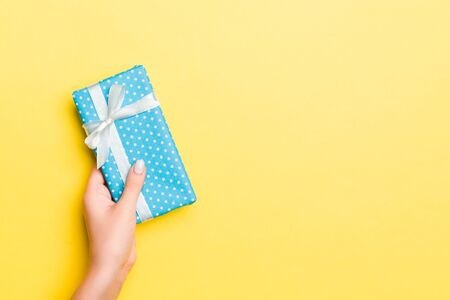 Woman arms holding gift box with colored ribbon on yellow table background, top view and copy space for you design.