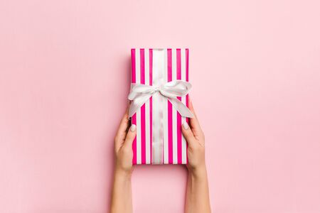 Females hands holding striped gift box with colored ribbon on living coral background. Christmas concept or other holiday handmade present box, concept top view with copy space.