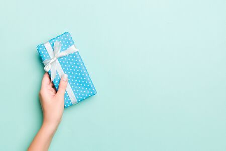 Woman hands give wrapped christmas or other holiday handmade present in colored paper. Present box, decoration of gift on Blue table, top view with copy space.