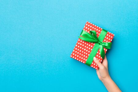 Woman arms holding gift box with colored ribbon on blue table background, top view and copy space for you design. Stock Photo