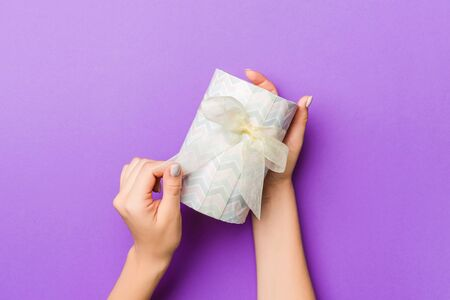 Flat lay of woman hands holding gift wrapped and decorated with bow on purple background with copy space. Christmas and holiday concept.