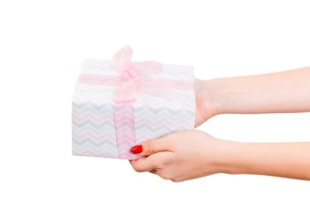 Woman hands give wrapped Christmas or other holiday handmade present in colored paper with pink ribbon. Isolated on white background, top view. thanksgiving Gift box concept. Zdjęcie Seryjne